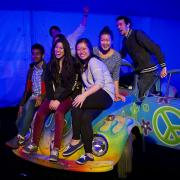 Guests sit on a vintage VW Beetle at the 70s and 80s party